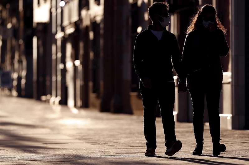 Una pareja cogida de la mano pasea por una calle. EFE/Archivo