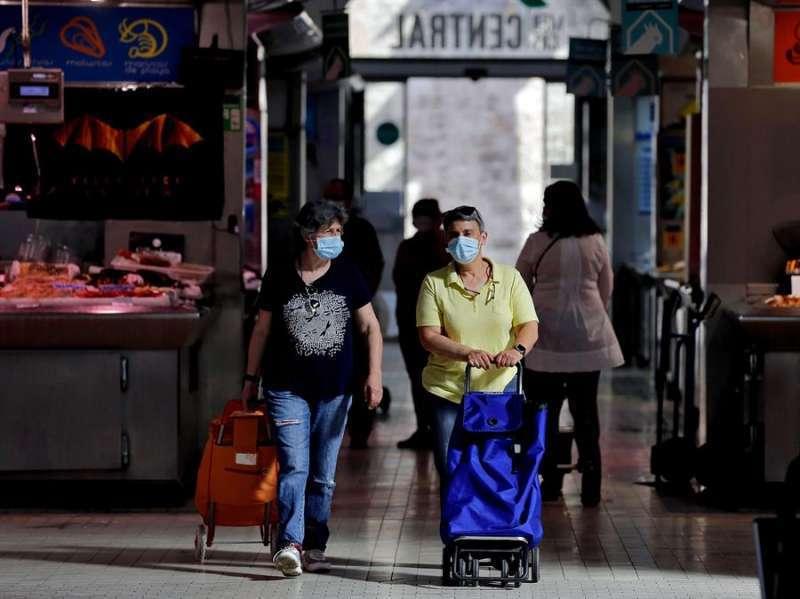 Varias personas realizan sus compras con mascarilla. EFE