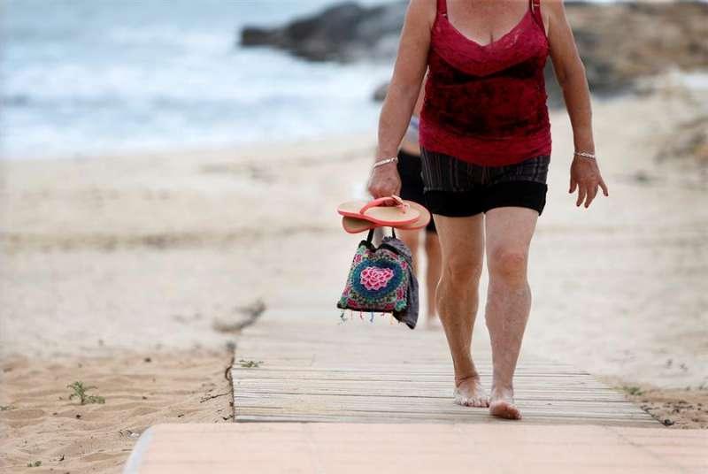 Dos mujeres salen de la playa tras pasear, en una imagen de estos días en Alicante. EFE/Manuel Lorenzo