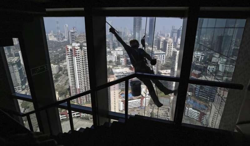 Un trabajador limpia las ventanas de un rascacielos. EFE