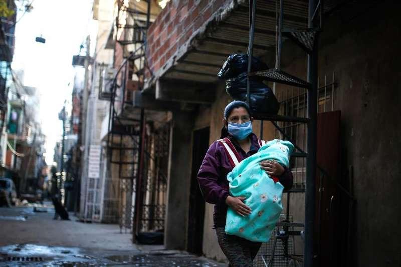 En la imagen, una mujer con mascarilla lleva a su bebé por una calle de la Villa 31, en Buenos Aires (Argentina). EFE/Juan Ignacio Roncoroni/Archivo