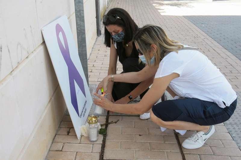Dos mujeres encienden velas durante una concentración por un asesinato machista.