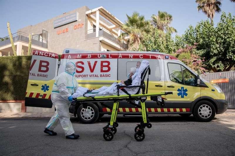 Un sanitario traslada a una anciana de una residencia donde se ha detectado un brote de covid. EFE