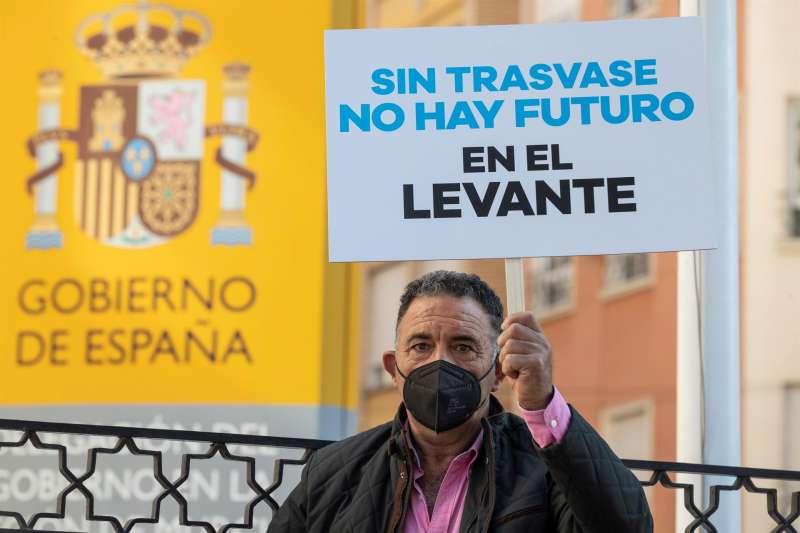 Un agricultor muestra una pancarta durante un momento de la concentración de agricultores, regantes y miembros del Circulo del Agua este jueves.EFE