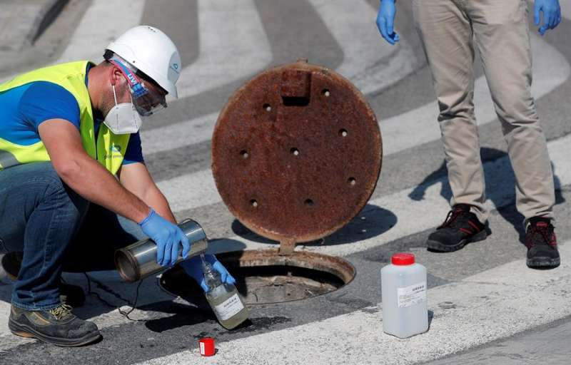 Dos técnicos de Global Omnium extraen una muestra de las aguas residuales de la ciudad para ser analizadas posteriormente y determinar la presencia de restos genómicos de COVID-19. EFE