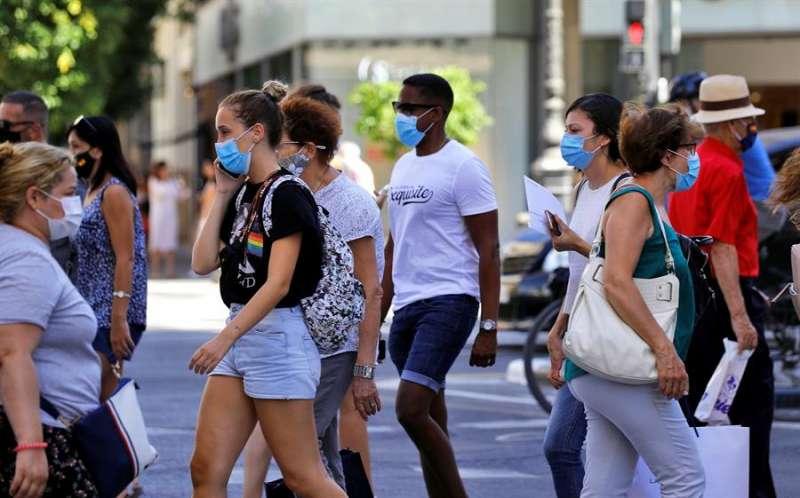 Varias personas, todas ellas con mascarilla, cruzan un paso de peatones en una calle de Valéncia. EFE