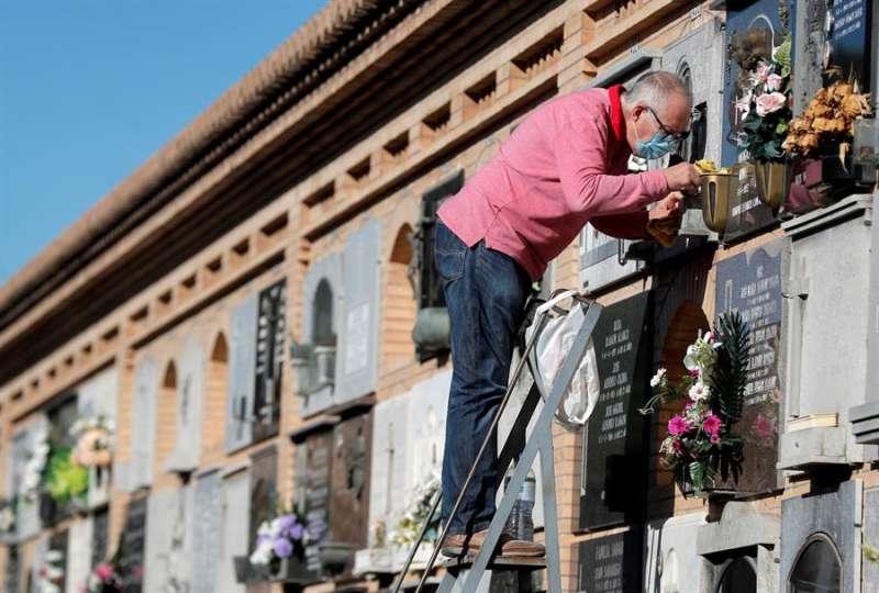 Una persona limpia una lápida, hoy en el Cementerio General de València