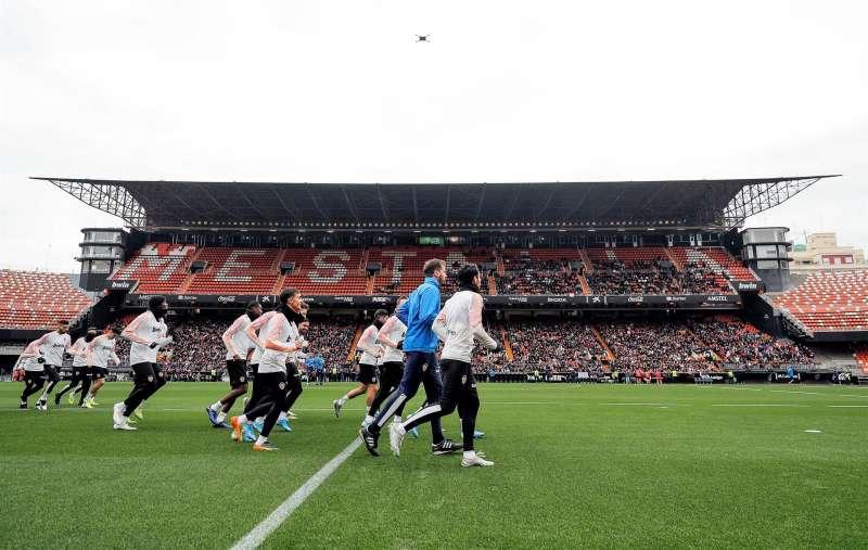 Los jugadores del Valencia CF corren por césped del estadio de Mestalla.