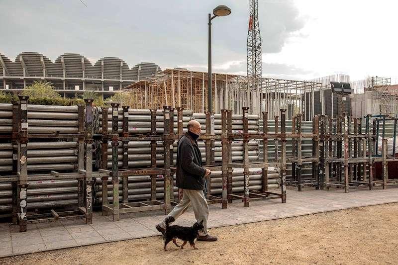 Una persona pasea a su perro frente a unas obras en València. EFE