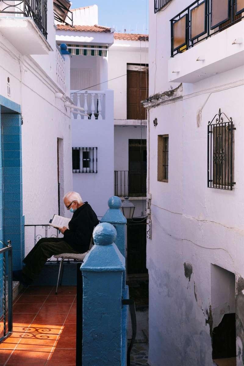 Un hombre lee un libro en la entrada de su casa. EFE