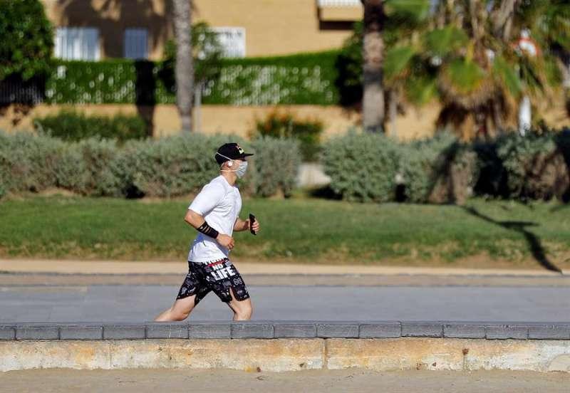 Un hombre hace deporte en la playa de La Patacona de Alboraya. EFE
