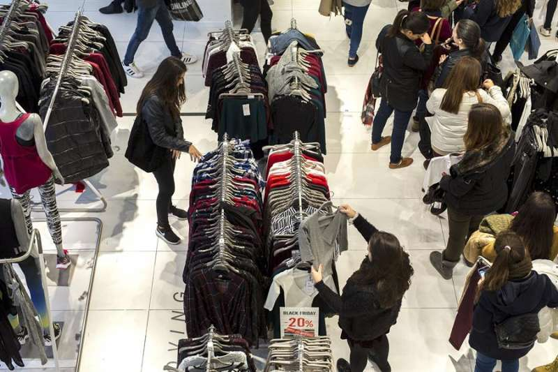 Varias personas realizan compras en una zona comercial de Valencia. EFE