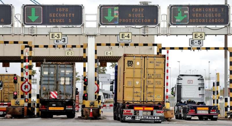 Varios camiones entran en el puerto de Valencia donde prosiguen los trabajos de carga y descarga de mercancías.