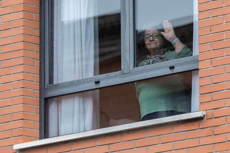 Una mujer saluda desde una residencia de mayores. EFE