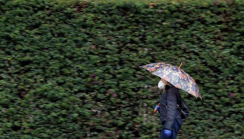 Una mujer se protege con un paraguas de la lluvia, en una imagen del pasado mes de abril, que ha sido cálido y húmedo. EFE