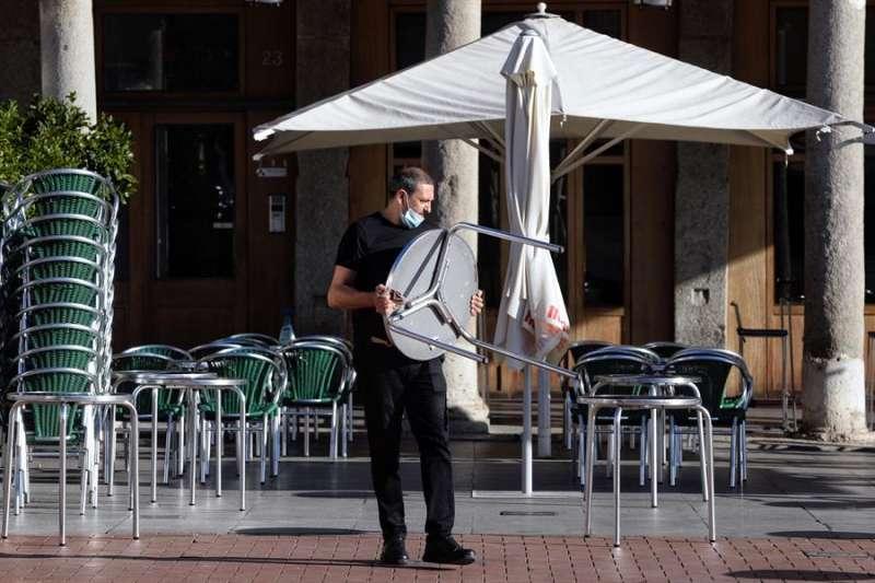 Un camarero coloca las mesas de una terraza. EFE
