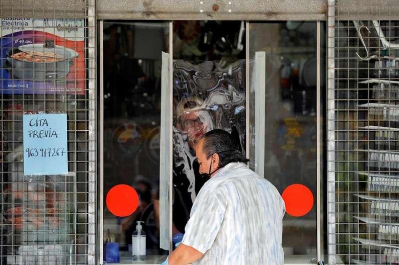 Un trabajador de una ferretería atiende a un cliente protegido por un plástico, en una imagen de estos días. EFE/Manuel Bruque