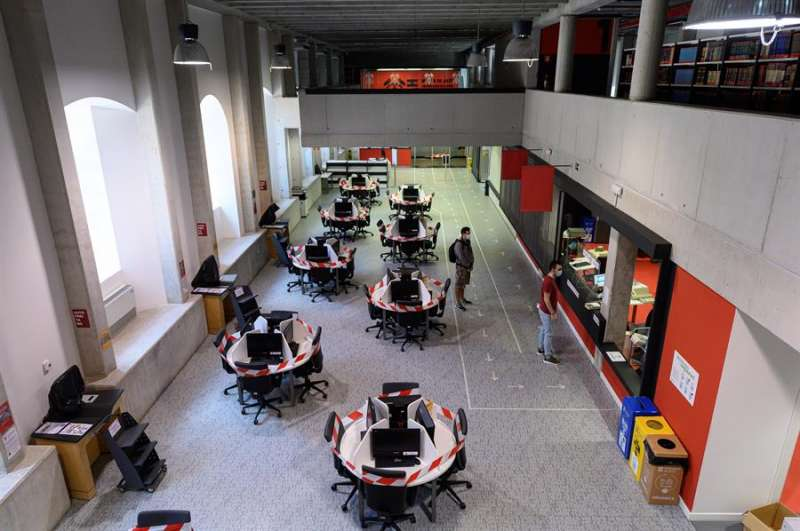 Varias mesas de ordenadores permanecen precintadas en la reapertura de una biblioteca universitaria. EFE