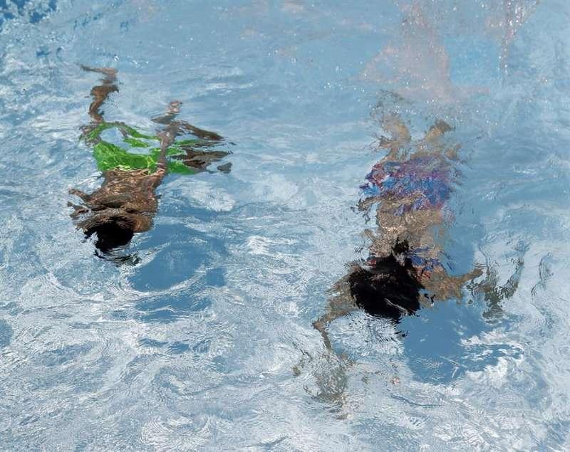 En la imagen, dos personas bucean en una piscina. EFE/J.J. Guillén/Archivo