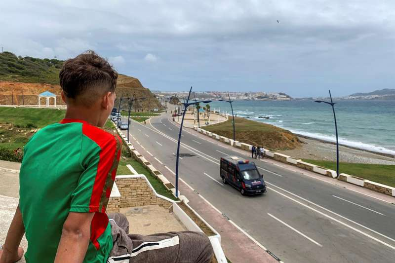 Un marroquí menor de edad observa este jueves Ceuta, al fondo, y en primer término la barrera establecida por las autoridades marroquíes para impedir el acceso de personas y vehículos civiles a la carretera marítima que une Fnidq (Castillejos) con Ceuta.