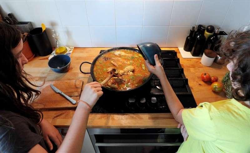 Dos niños cocinan una paella valenciana en la cocina de su casa con motivo del Día Mundial de la Paella que se celebra este domingo. EFE