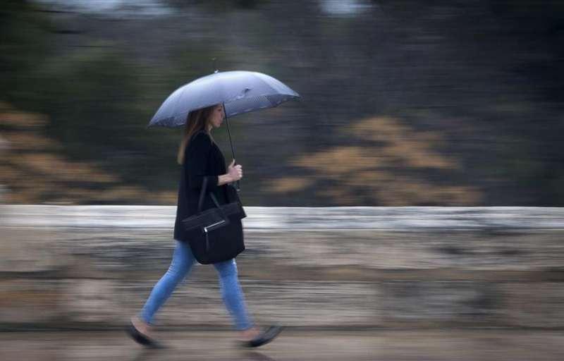 Una joven se protege con un paragua. EFE