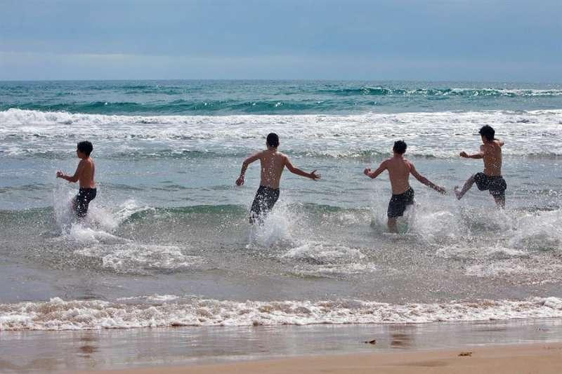Varios jóvenes disfrutan del mar, este lunes, en la playa de Gandía en el primer día de la fase 2 de toda la Comunitat Valenciana. EFE