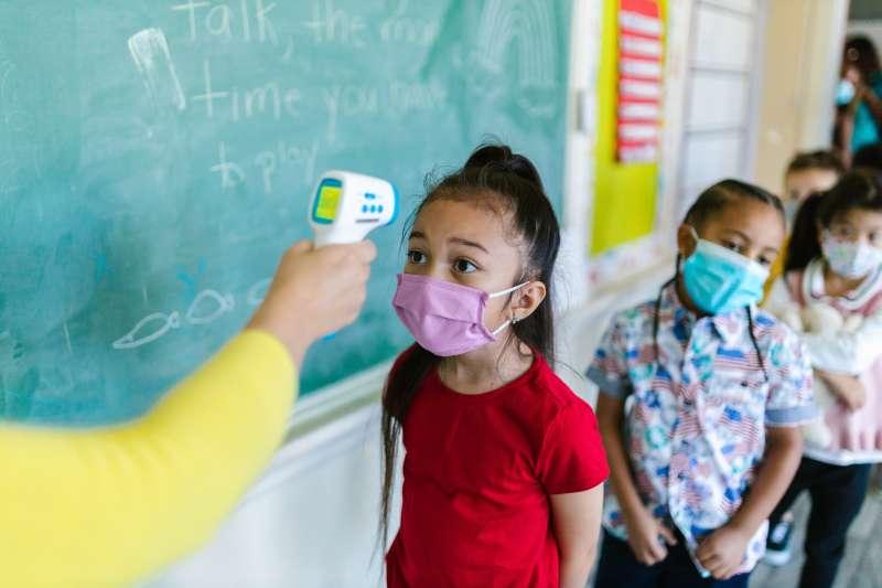 Miden la temperatura a una niña en un aula. Archivo