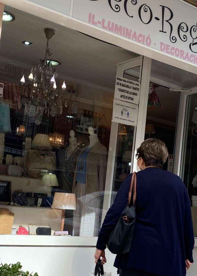 Mujer observando el escaparate de un comercio local de Quart de Poblet.
