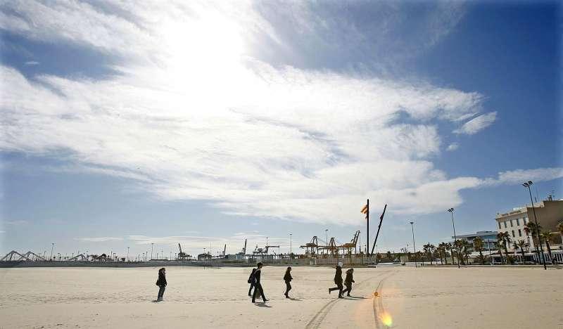 Varios jóvenes pasean este mediodía por la playa de Las Arenas de Valencia para disfrutar de un día soleado.
