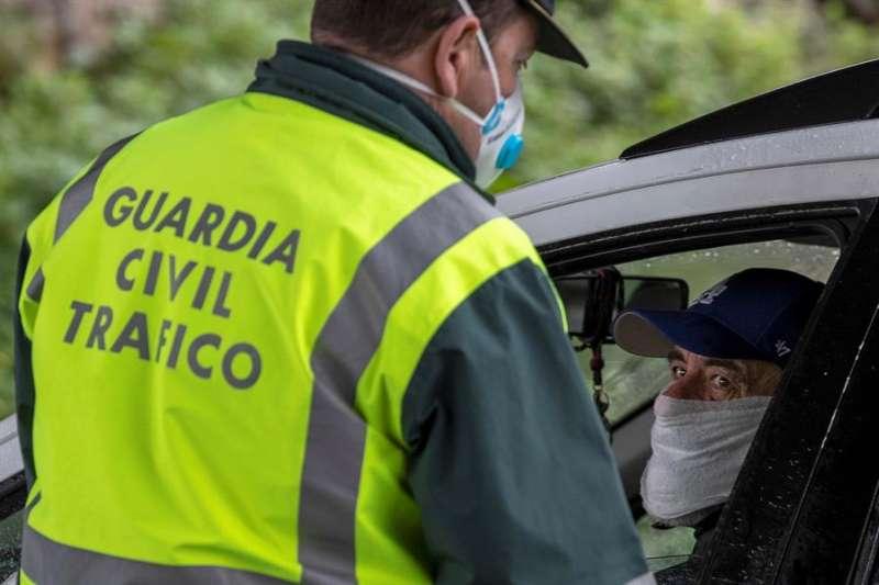 Un agente de la Guardia Civil de Tráfico conversa con un conductor con mascarilla durante un control. EFE/Julio Muñoz