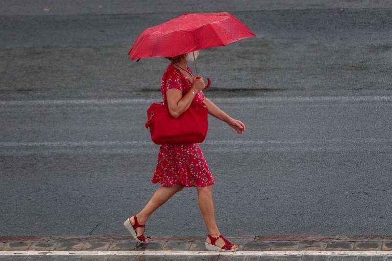 Una mujer camina bajo la lluvia. EFE/ Biel Aliño/Archivo