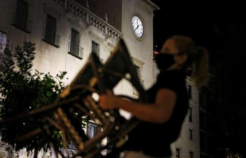 Una trabajadora de hostelería recoge su terraza en Alicante antes del toque de queda. EFE/Manuel Lorenzo/Archivo