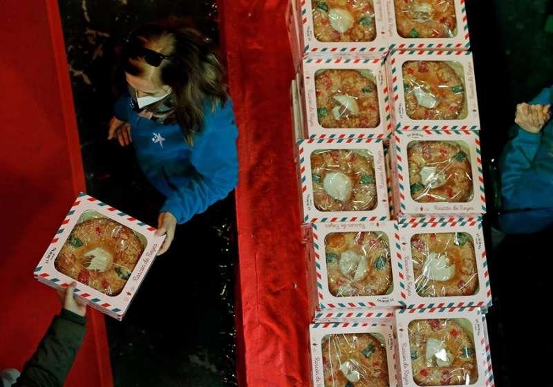 Una persona reparte decenas de roscones de reyes en las instalaciones el campo de Mestalla (Valencia) para cerca de 300 familias sin recursos citados previamente por el Banco de Alimentos. EFE/ Juan Carlos Cárdenas