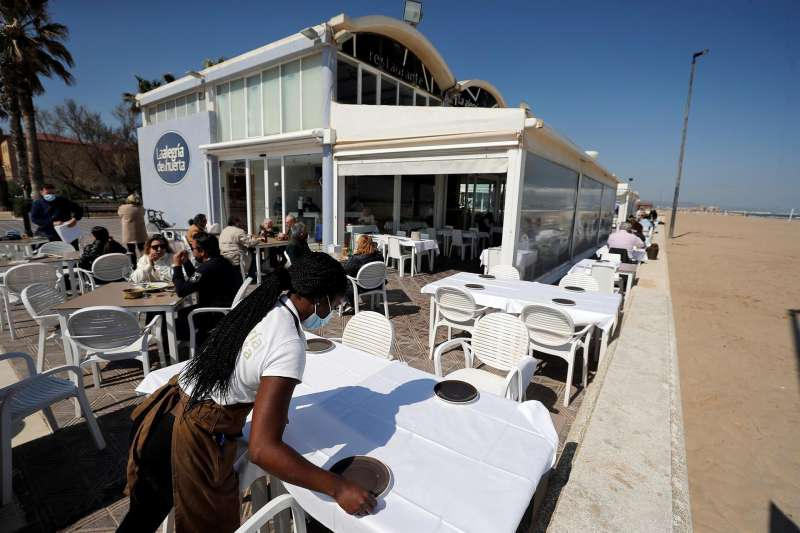 Una camarera prepara una mesa en una terraza en uno de los restaurantes de la playa de la Malvarrosa de Valéncia.