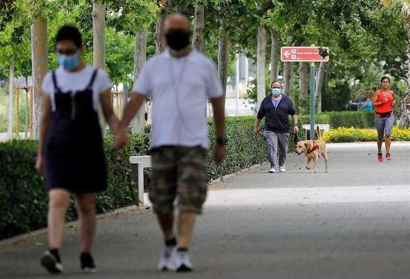 Dos personas caminan con mascarillas.