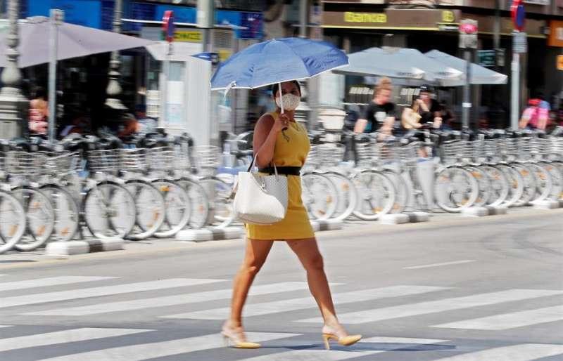 Una mujer se protege del calor con una sombrilla en una imagen de archivo. EFE/Kai Försterling
