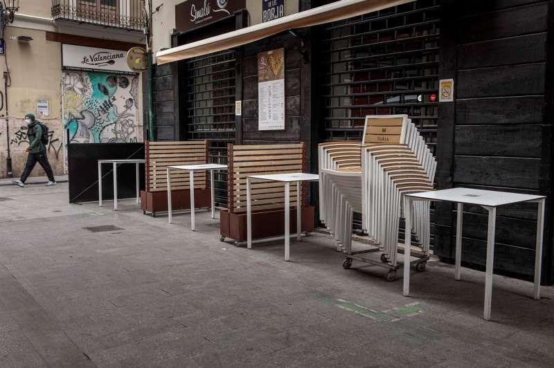 La terraza de un restaurante con las sillas y mesas ya recogidas.