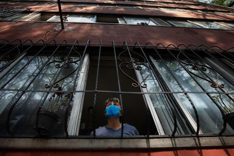 Persona con mascarilla mira a través de la ventana de su domicilio