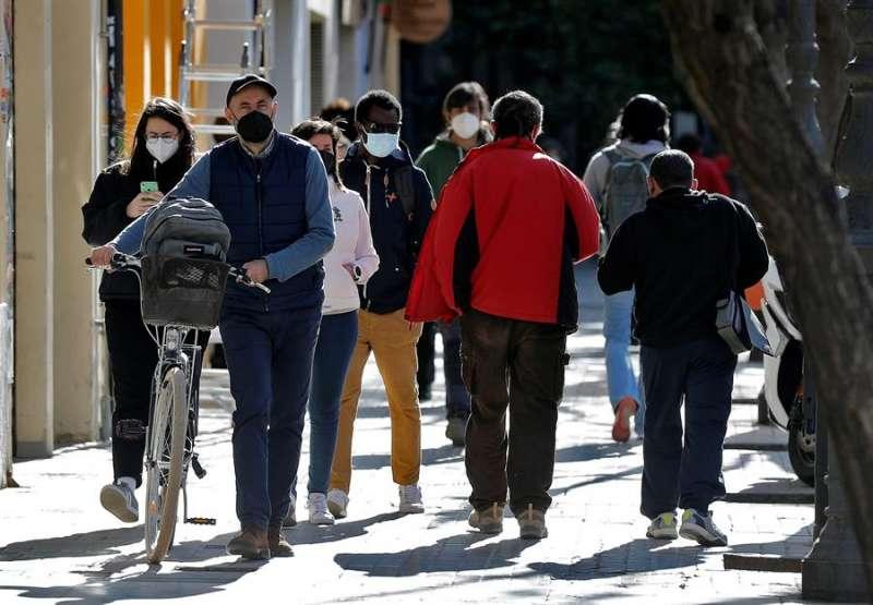 Varias personas caminan por la calle con mascarillas. EPDA