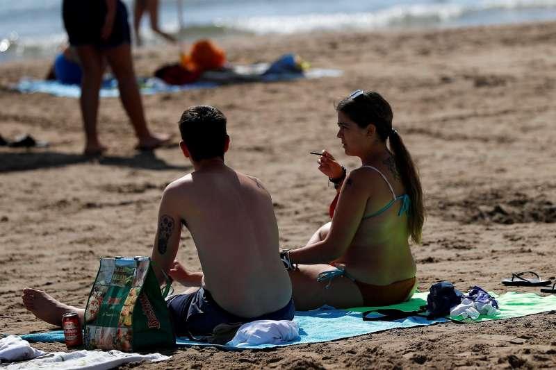 Una joven fuma en la playa de La Patacona de Alboraia. EFE/Manuel Bruque/Archivo