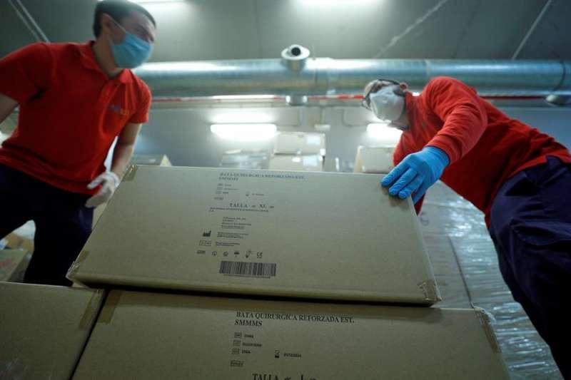 Operarios del hospital La Fe de València, desembalan el material sanitario (guantes, mascarillas y monos de protección) que llegó de madrugada procedente de China. EFE/Manuel Bruque