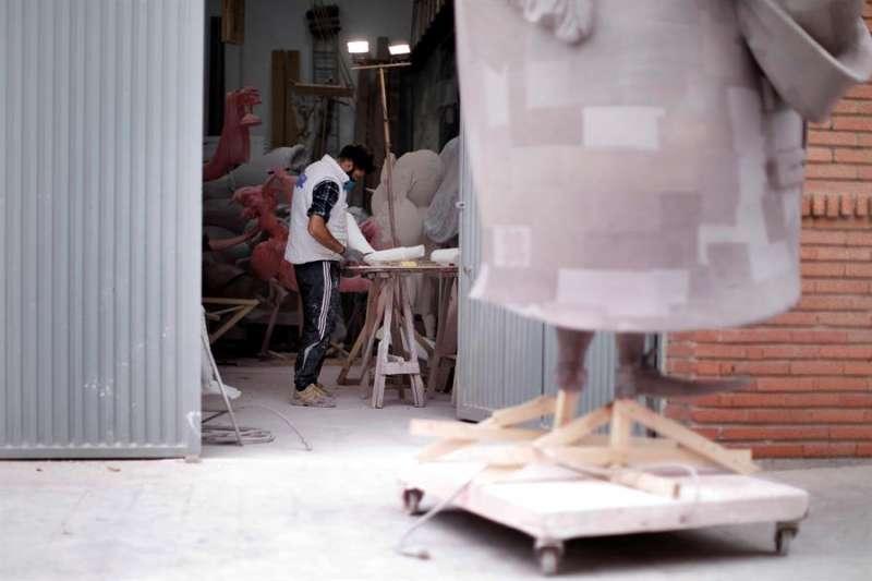 Un artista fallero trabaja en un monumento que este año no será montado cuando este domingo, día de la Crida, se iniciarán unas Fallas enteramente virtuales. EFE/Biel Aliño