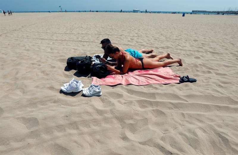 Una pareja toma el sol en la playa de la Malvarrosa manteniendo una amplia distancia social con el resto de usuarios durante este miércoles. EFE