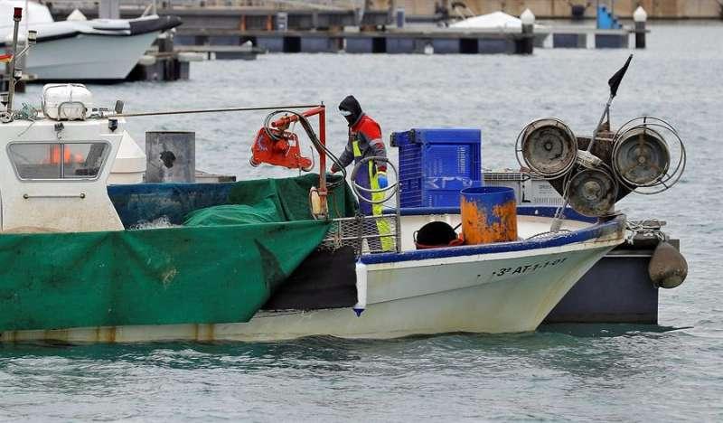 Marineros protegidos con mascarillas en su barco en un puerto valenciano. EFE/Manuel Bruque/Archivo