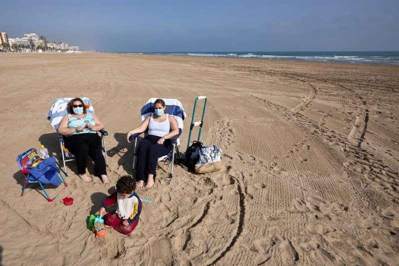 Varias personas toman el sol en la playa de Gandia