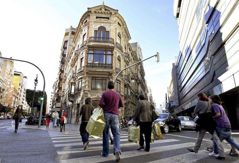 Varias personas caminan con sus compras por una calle del centro de València. EFE/Archivo