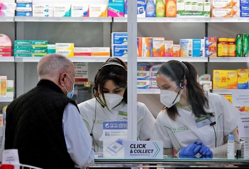 Dos empleadas de una farmacia atienden a un cliente. EFE/ Manuel Bruque/Archivo
