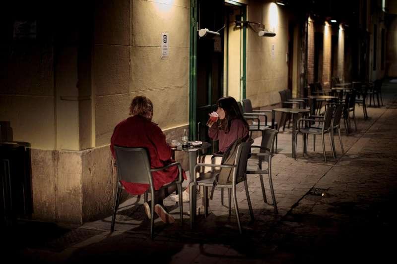 Dos jóvenes consumen unas bebidas en una terraza semi vacía de un bar de una céntrica plaza de València, en plena pandemia.