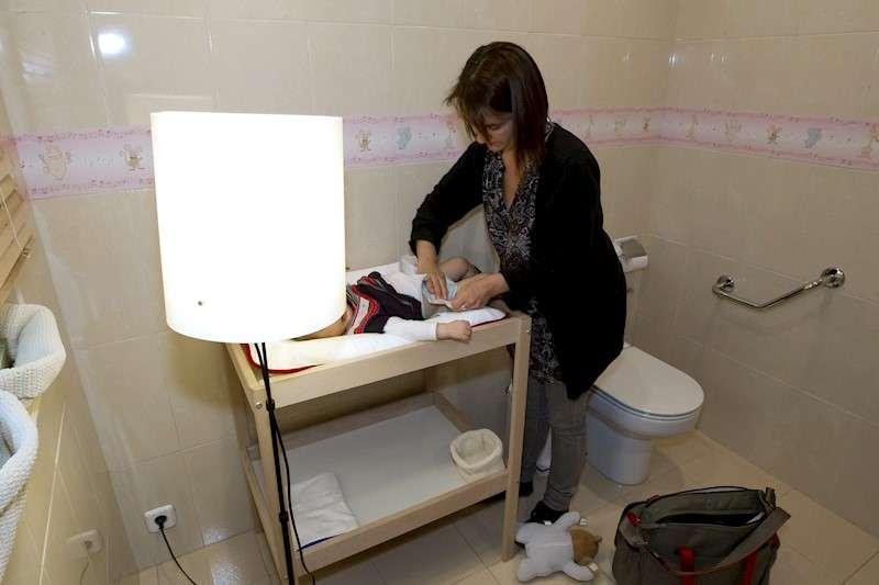 Imagen de archivo de una mujer cambiando el pañal a su bebé. EFE/Archivo